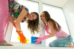 Girls washing the window Royalty Free Stock Photo
