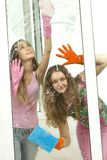 Girls washing the window with mops Stock Images
