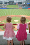 Girls Watching Baseball Game. Two little girls watch a baseball game Stock Photography