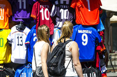 Girls watching football shirts on display. Florence, Italy - June 28, 2014: girls watch football shirts on display in a local market stall in the heart of Royalty Free Stock Photos