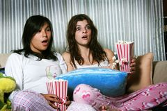 Girls watching horror movie. Two teenage girls gasp as they watch a horror movie together, gripping the popcorn in their hands Royalty Free Stock Image
