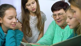 Girls watching old photo album with their grandmother. Senior woman showing vintage photos to children. Family, relationship and communication stock video footage