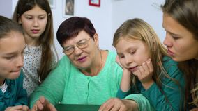 Girls watching old photo album with their grandmother. Senior woman showing vintage photos to children. Family, relationship and communication stock footage