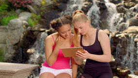 Girls watching photo on tablet outdoor. Young woman sitting near waterfall. And using tablet computer. Multicultural friends having fun with ipad at park. Happy stock video