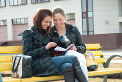Girls watching photos in album Royalty Free Stock Photography