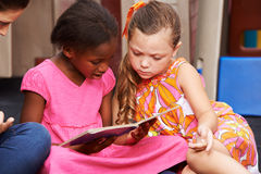 Girls watching picture book in kindergarten Royalty Free Stock Images