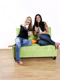 Girls watching shocking TV. Two girls laughing while watching tv and having snacks on the couch Stock Photo