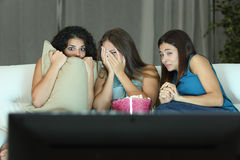 Girls watching a terror movie on tv. Sitting on a couch at home Royalty Free Stock Image