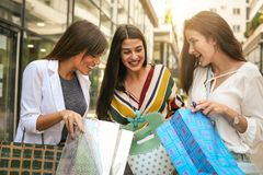 Girls watching their  new clothes. Stock Photos