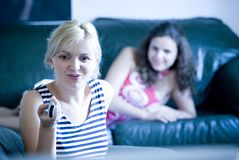 Girls watching tv. A blond and brunette sit watching tv Royalty Free Stock Image