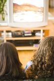 Girls watching tv. Two girls watching television together Stock Photography
