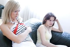 Girls watching tv. Two girls sit watching tv on the sofa Royalty Free Stock Photo