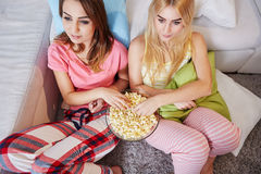 Girls watching tv eating popcorn. Portrait from above of two pretty women watching tv eating popcorn Royalty Free Stock Images