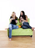 Girls watching TV laughing. Two girls laughing while watching tv and having snacks on the couch Royalty Free Stock Image