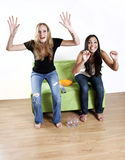 Girls watching TV sports. Two excited girls jumping up from couch cheering Stock Images