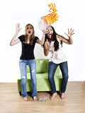 Girls watching TV sports. Two excited girls jumping up from couch cheering Royalty Free Stock Image
