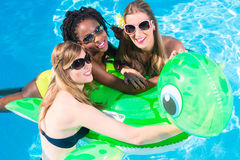 Girls in water of swimming pool with inflatable anmimal Royalty Free Stock Photo