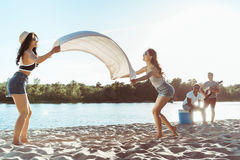 Girls waving beach blanket on sandy riverside at daytime Royalty Free Stock Image