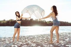 Girls waving beach blanket on sandy riverside at daytime Royalty Free Stock Photos