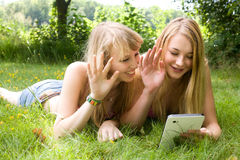 Girls waving with a tablet Royalty Free Stock Image