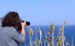 Girls with wavy hair holding a camera on the horizon in the sea. royalty free stock images