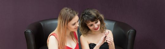 Girls wear a gold ring on their finger. Two girls try on jewels gold rings with stones royalty free stock photography