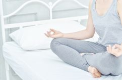 Girls wear gray shirts and pants, sitting on yoga on the mattress. stock images