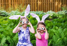 Girls Wearing Bunny Ears and Silly Egg Eyes - Close Up. A funny portrait of two girls having fun on Easter wearing bunny ears and holding up silly eyes made from Royalty Free Stock Photography