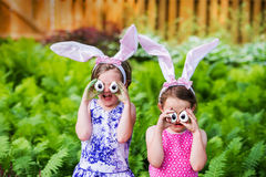 Girls Wearing Bunny Ears and Silly Egg Eyes - Close Up. A funny portrait of two girls having fun on Easter wearing bunny ears and holding up silly eyes made from Royalty Free Stock Photos