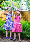 Girls Wearing Bunny Ears and Silly Egg Eyes. A funny portrait of two girls having fun on Easter wearing bunny ears and holding up silly eyes made from eggs Royalty Free Stock Photo