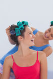 Girls wearing hair rollers sitting in bed Stock Photography