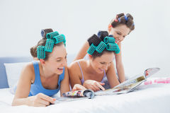 Girls wearing pajamas and hair rollers sitting in bed with magaz Stock Photo