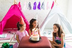 Girls Wearing Party Hats With Birthday Cake On Table. Cute girls wearing party hats with birthday cake on table against tipi tents at home stock images