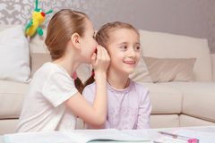 Girls whisper into each other ears Stock Photography