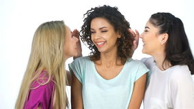 The girls whisper in the ear of girlfriend. And laughing. Three girls exhibit different emotions on a white background. Asian, caucasian, african or african stock footage