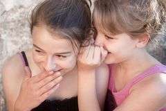Girls whispering secrets. To pretty teenage girls gossiping, giggling and whispering Stock Photo