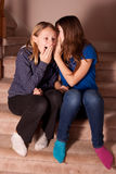 Girls whispering surprising secrets. Two young girls sitting on the stairs in a home telling secrets and reacting with surprise Royalty Free Stock Photography