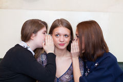 Girls whispering to a friend Stock Photo