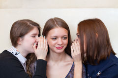 Girls whispering to a friend Royalty Free Stock Photography