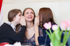 Girls whispering to a friend Royalty Free Stock Images