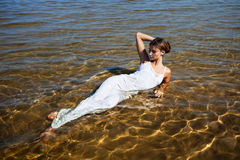 Girls in white dress lying in water Stock Photo