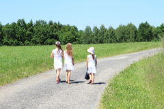 Girls in white dresses on road stock image