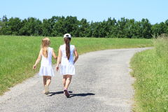 Girls in white dresses on road. Two little kids - girls in white dresses walking on concrete road among meadows to forest royalty free stock photography