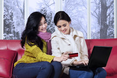 Girls in winter clothes shopping online Royalty Free Stock Photos