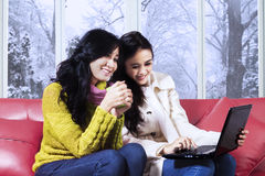 Girls in winter clothes using laptop Stock Images