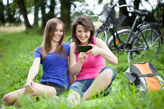 Girls With Smartphone On A Glade Royalty Free Stock Photo