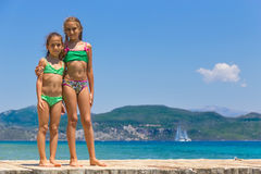 Girls on the wooden pier in the sea Stock Photos