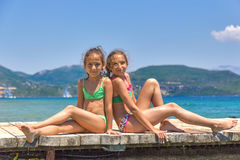Girls on the wooden pier in the sea stock photography