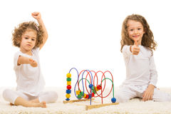Girls with wooden toy giving thumbs up Royalty Free Stock Photo