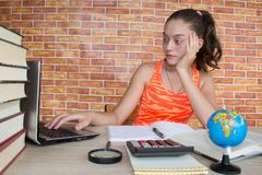 Girls work on his homework. Young Girl studying on desk at home Royalty Free Stock Image